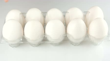 empaque : Large white chicken eggs in a transparent plastic tray on a white background. Female hands touch each the eggs in the tray.