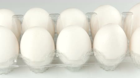 Large white chicken eggs in a transparent plastic tray on a white background.
