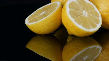 limonada : Big fresh yellow lemons on black mirror surface on a black background close up view.