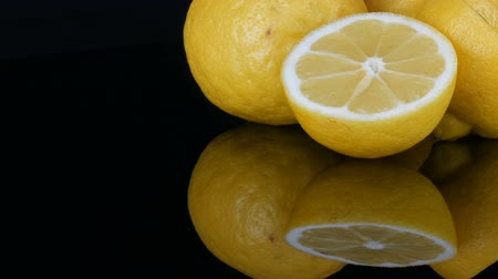 cítrico : Big fresh yellow lemons on black mirror surface on a black background close up view.