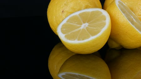 Big fresh yellow lemons on black mirror surface on a black background close up view.