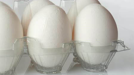Large white chicken eggs in transparent plastic tray on a white background