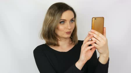 Portrait of a beautiful young sexy elegant woman in a black dress who takes a selfie on a smartphone and admire herself against a white background Stock Footage