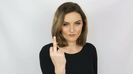 Beautiful sexy bitch girl with flowing hair and blue eyes gently looks into the camera and then shows a fuck sign on a white background. Female aggression