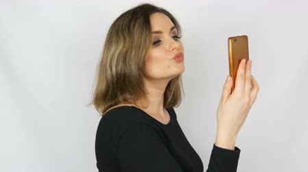 Portrait of a beautiful young sexy elegant woman in a black dress who speaks on a smartphone and admire herself against a white background Vídeos
