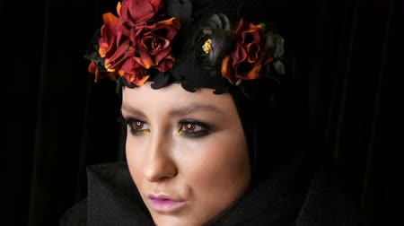 kırmızı şarap : Professional girl model with beautiful makeup poses in a black cap and wreath on her head in front of the camera on black background in the image of a black widow. High-fashion Stok Video