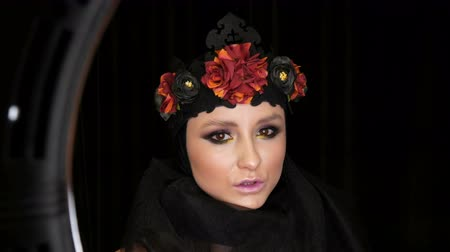 posando : Professional girl model with beautiful makeup poses in a black cap and wreath on her head in front of the camera on black background in the image of a black widow. High-fashion Stock Footage