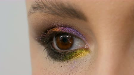 füstös : Fashionable multi-colored eye shadow chameleon with yellow purple gray silver color on the eyelid of beautiful girl model with brown eyes. Professional cosmetic makeup. Eye close up view