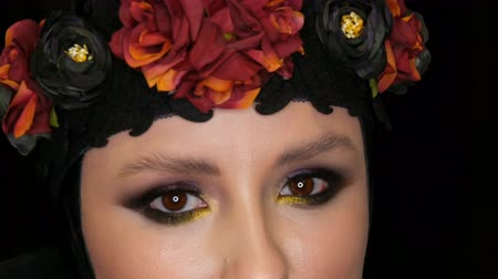 reflektör : Professional girl model with beautiful makeup poses in a black cap and wreath on her head in front of the camera on black background in the image of a black widow. High-fashion Stok Video