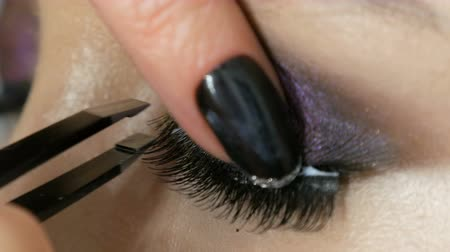 pastas : Professional make-up artist pastes false long black eyelashes on the model eye, which is colored with different color eye shadows. Stock Footage