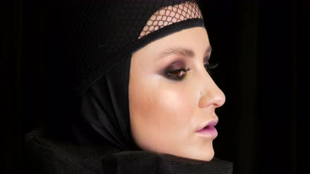 reflektör : Professional girl model with beautiful makeup poses in a black cap on her head in front of the camera on black background in the image of a black widow. High-fashion Stok Video