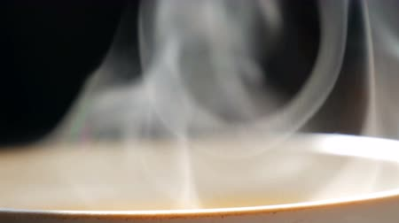 csészealj : Trickle of Steam Slowly Rising from the Cup of tea close up view. White steam rises light, graceful twists on black background Stock mozgókép