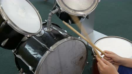 cymbals : The teenager is learning to play drum set. Drum sticks knock on different drums cymbals