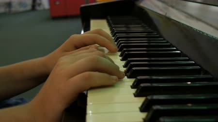 ebano : Hands teenage boy playing piano keys close up view