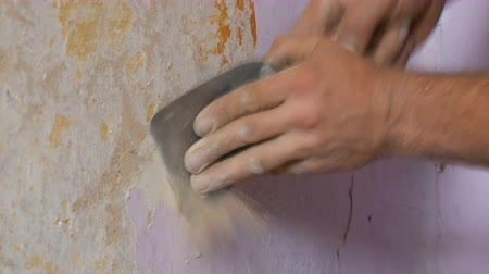 scrape : Decrepit pink wallpaper on a wall, home repair. Man peeling old wallpaper with special spatula. Stock Footage