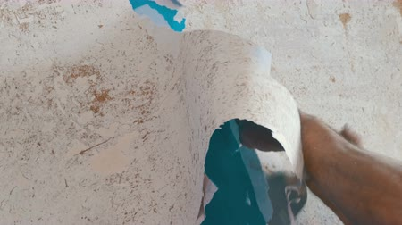 scrape : Man cleans or peels the wall from old wallpaper