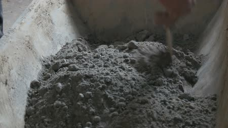 kov : Male builder making cement. Blends cement clay and water, mixing all it