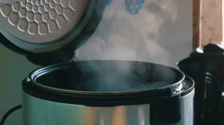 lids : Steam in a cooking multicooker with an open lid in a kitchen