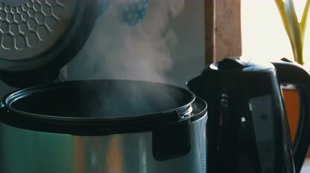 fedél : Steam in a cooking multicooker with an open lid in a kitchen