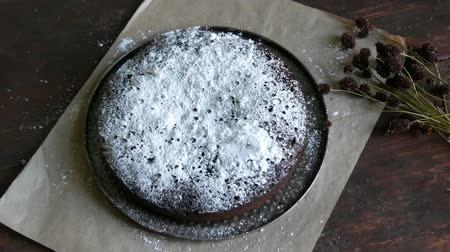 geçiştirmek : Homemade freshly baked chocolate brownie cake powdered with icing sugar lies next to the stylish dried meadow flowers Stok Video