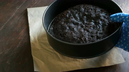muffin : Female hand in blue kitchen glove puts freshly baked homemade chocolate brownie cake on the table