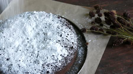 šlehačka : Homemade freshly baked chocolate brownie cake powdered with icing sugar lies next to the stylish dried meadow flowers Dostupné videozáznamy
