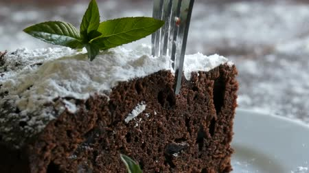 fondant : Homemade baked chocolate brownie cake muffled with powdered sugar on a white plate decorated with mint leaves. Fork breaks off piece of brownie pie from the plate Stock Footage