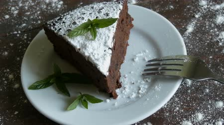 muffin : A piece of chocolate brownie cake on a white plate decorated with fresh mint leaves next to fork