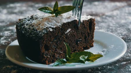 šlehačka : Homemade baked chocolate brownie cake muffled with powdered sugar on a white plate decorated with mint leaves. Fork breaks off piece of brownie pie from the plate Dostupné videozáznamy