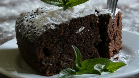 lanches : Homemade baked chocolate brownie cake muffled with powdered sugar on a white plate decorated with mint leaves. Fork breaks off piece of brownie pie from the plate Stock Footage