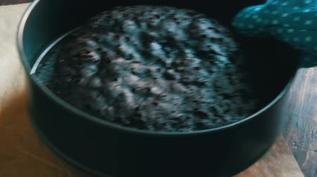 muffin : Female hand in blue kitchen glove takes freshly baked homemade chocolate brownie cake on the table