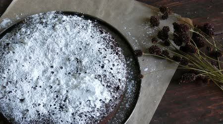 домовой : Homemade freshly baked chocolate brownie cake powdered with icing sugar lies next to the stylish dried meadow flowers Стоковые видеозаписи