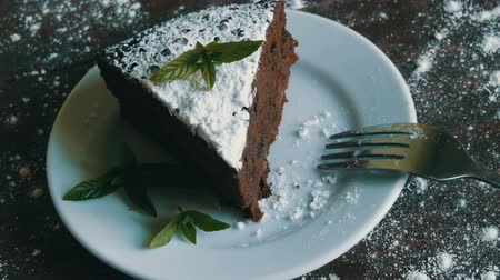 fondant : A piece of chocolate brownie cake on a white plate decorated with fresh mint leaves next to fork