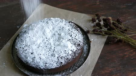 muffin : Homemade freshly baked chocolate brownie cake powdered with icing sugar lies next to the stylish dried meadow flowers Stock Footage