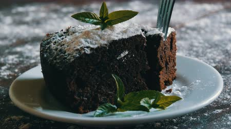 muffin : Homemade baked chocolate brownie cake muffled with powdered sugar on a white plate decorated with mint leaves. Fork breaks off piece of brownie pie from the plate Stock Footage