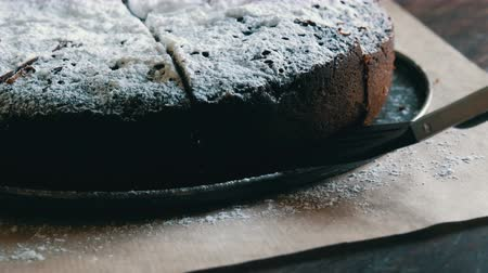 šlehačka : Special tongs for baking take piece of freshly baked chocolate brownie cake powdered with icing sugar