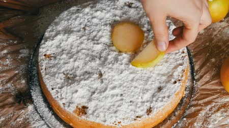 pão de especiarias : Female hand puts apple slices on delicious traditional freshly baked homemade gingerbread apple pie Charlotte richly powdered sugar top view Stock Footage