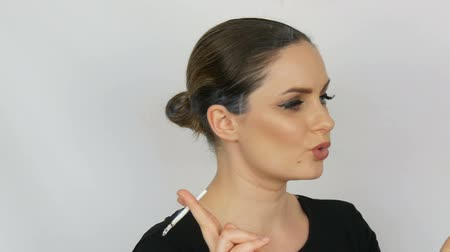 tartó : Portrait of a beautiful elegant young woman in a black dress with smooth bunned hair and classic make-up with big black arrows, smoking a ladys thin cigarette on a white background.