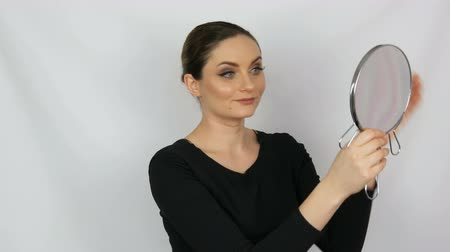 brow : Beautiful elegant sexy young woman holding a round mirror in her hands and looking into it admiring herself on a white background. Stock Footage
