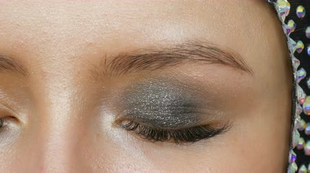 füstös : Makeup artist makes models smoky eyes with the help of special brush gray eyeshadow, eyes and eyelashes of girl close up view. Professional high fashion.