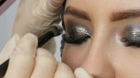 füstös : Professional high fashion. Makeup artist makes models smoky eyes with the help of special gray eyeshadow, eyes and eyelashes of a girl close up view.
