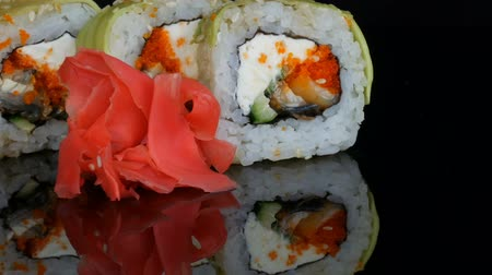 わさび : Green Dragon Sushi rolls and pink ginger. Sushi roll with salmon, vegetables and avocado closeup. Japan restaurant menu on a mirror surface against a black background. Japanese cuisine in studio 動画素材