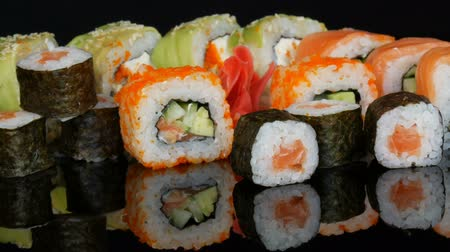 california rolls : A variety of colored sushi rolls sets and ginger on the mirror surface on a black background. Japanese cuisine in studio