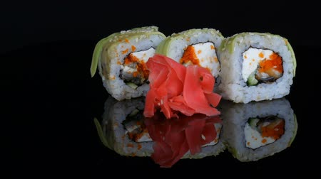 нори : Green Dragon Sushi rolls and pink ginger. Sushi roll with salmon, vegetables and avocado closeup. Japan restaurant menu on a mirror surface against a black background. Japanese cuisine in studio Стоковые видеозаписи
