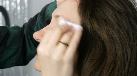 rouge : Professional make-up artist prepares the skin before make-up. Face of a middle-aged adult woman cleaned with cotton pad before make-up Stock Footage