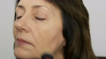 салоны красоты : Make up artist do makeup with highlighter concealer to middle-aged woman with blue eyes. Age makeup. Close-up portrait. Apply powder with brush