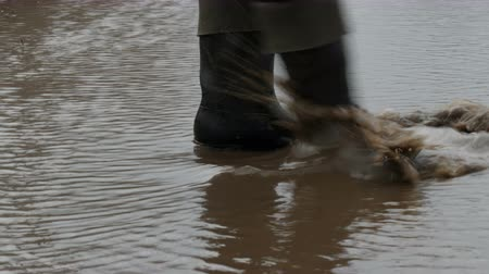 pegadas : A man walks through the muddy puddle in rubber boots. Stock Footage
