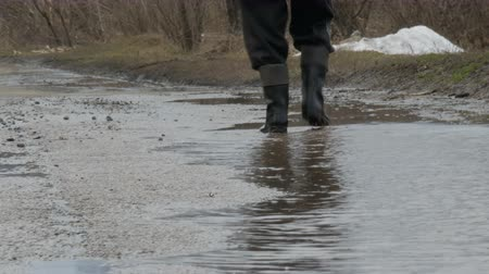 ślady stóp : A man walks through the muddy puddle in rubber boots. Wideo