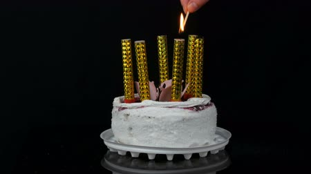 pozdravit : Womens hands light candle on a beautiful stylish sweet fresh white cake with cherry jam decorated with cream and coconut flakes on top. Birthday cake on black background.