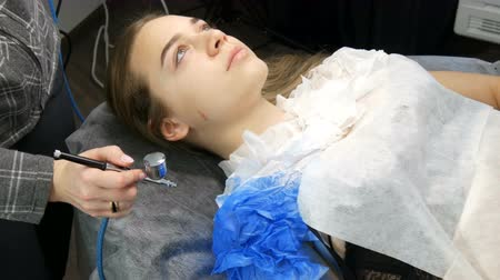 запомнить : Fashion studio, the model is preparing for the show. Teen girl lies on a special couch, designer prepares her image using a special airbrush spray with blue paint